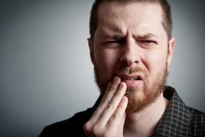 Man with a pained look holding the side of his mouth.