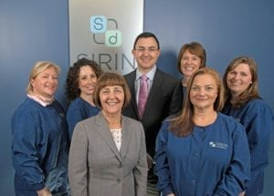 The entire staff of Dr. Sirin smiling for the camera in the office.