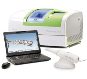 an image of a laptop computer showing a virtual model of a quadrant of teeth. Also the intraoral camera in its cradle, with a milling machine in the background