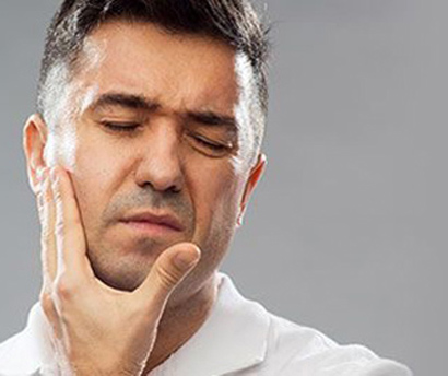 Dark-haired man holding the right side of his face in pain; for information on emergency dentistry from Dr. Sirin in Elgin, IL